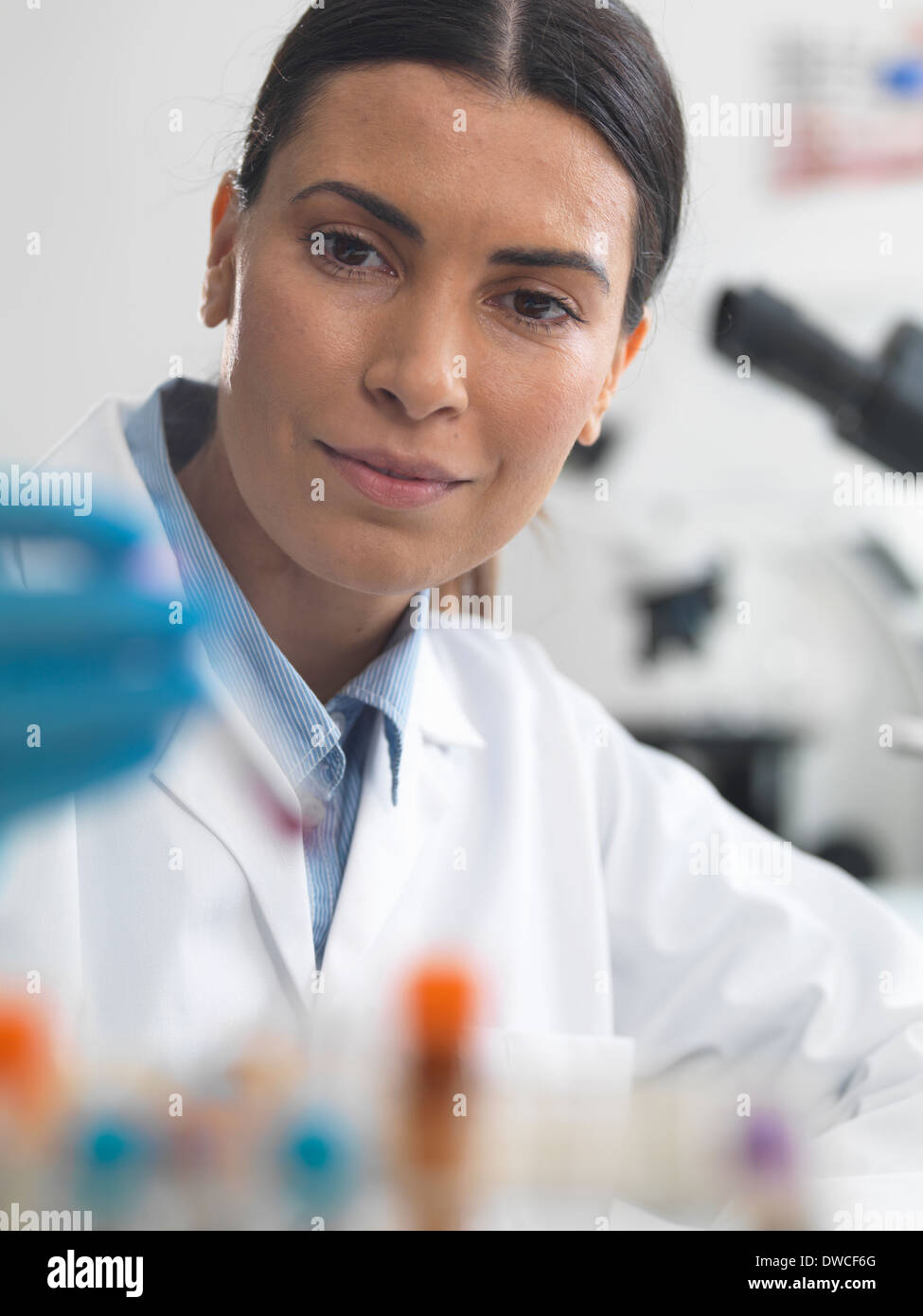 Female scientist about to view a sample under a microscope - Stock Image