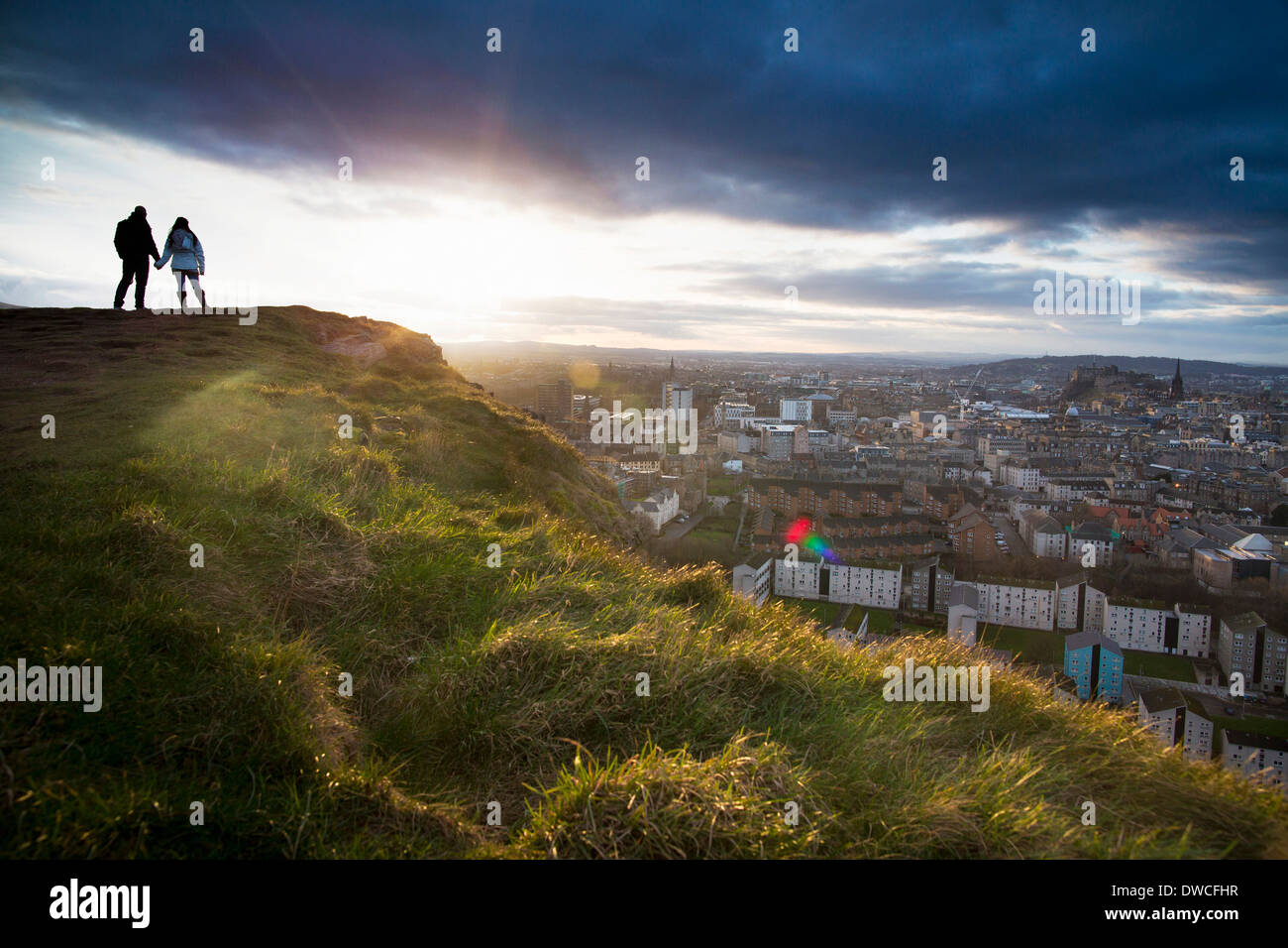 A young couple hold hands in front of the view of the City of Edinburgh from Salisbury Crags - Stock Image