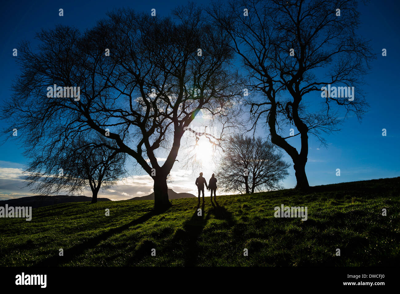 A young couple hold hands on Calton Hill in Edinburgh, capital of Scotland - Stock Image
