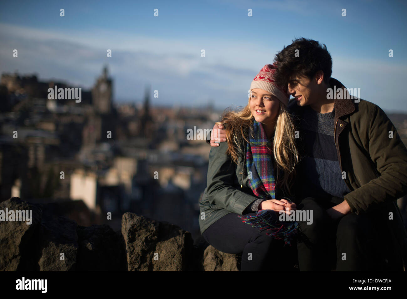 A young couple hug on Calton Hill with the background of the city of Edinburgh, capital of Scotland - Stock Image