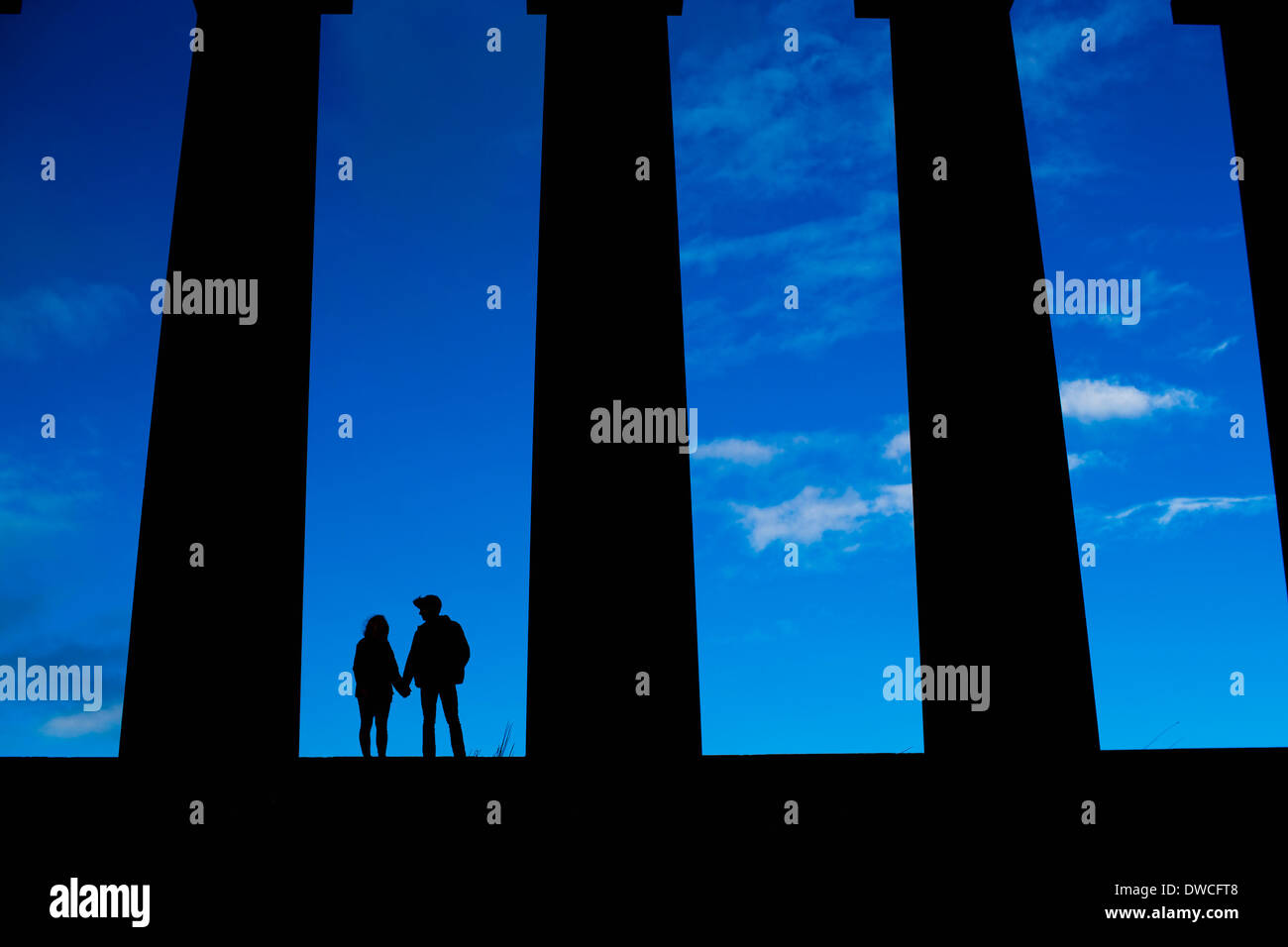 A young couple hold hands on the National Monument of Scotland on Calton Hill in Edinburgh - Stock Image