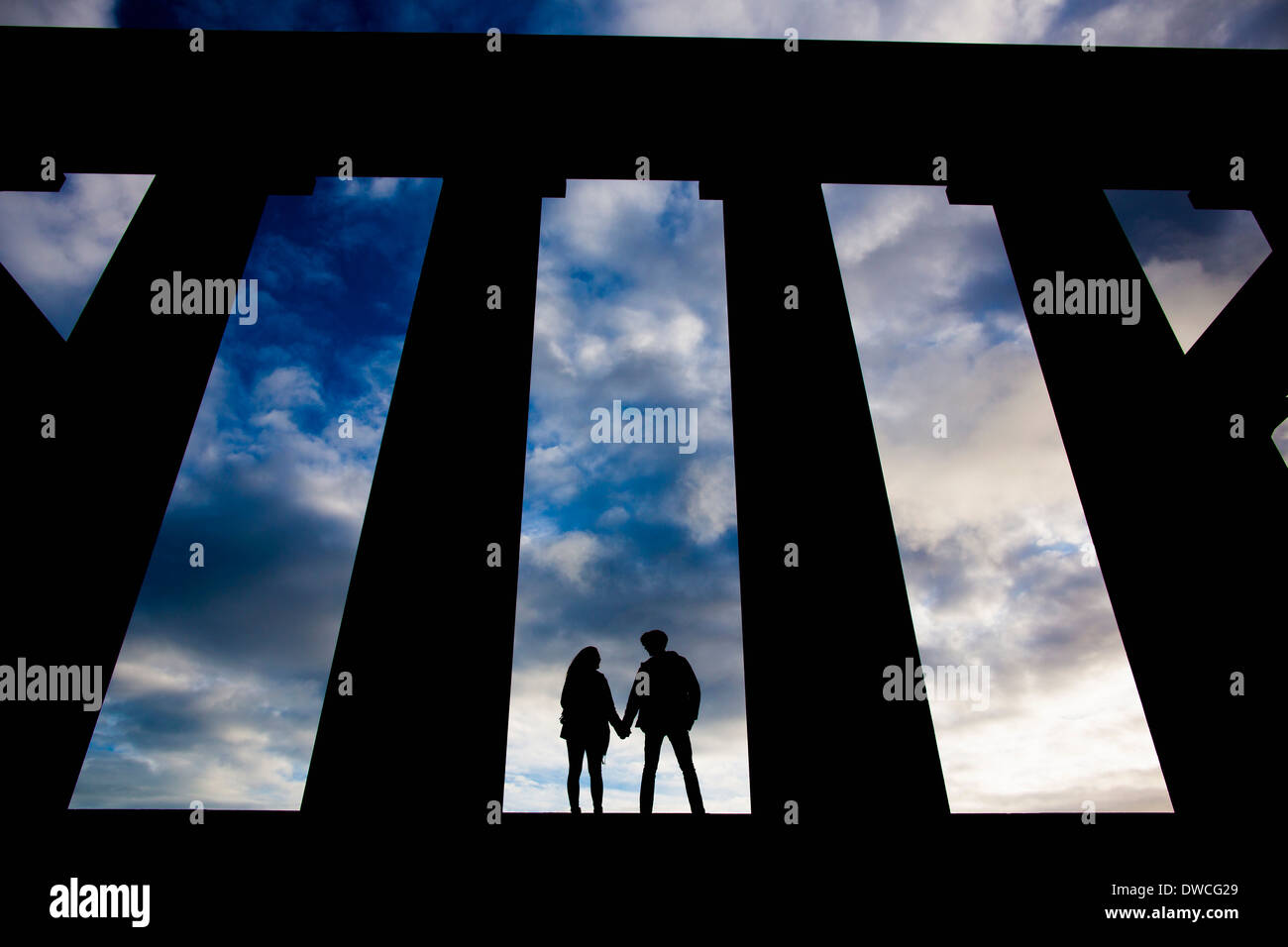 A young couple hold hands at the National Monument on Calton Hill in Edinburgh, Scotland - Stock Image