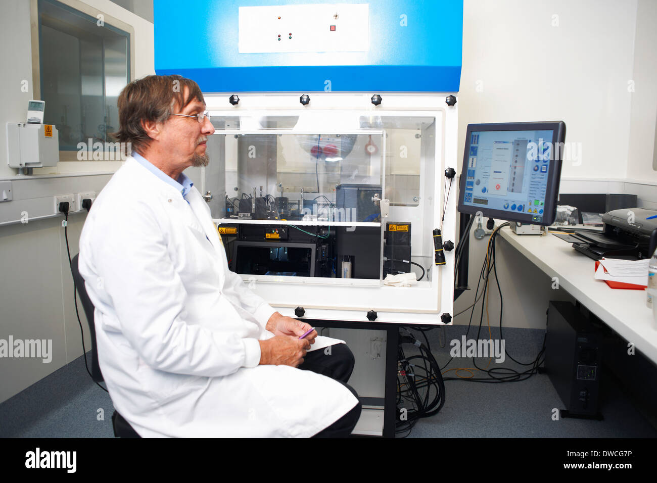 Scientist working in lab with computer and scientific machine - Stock Image