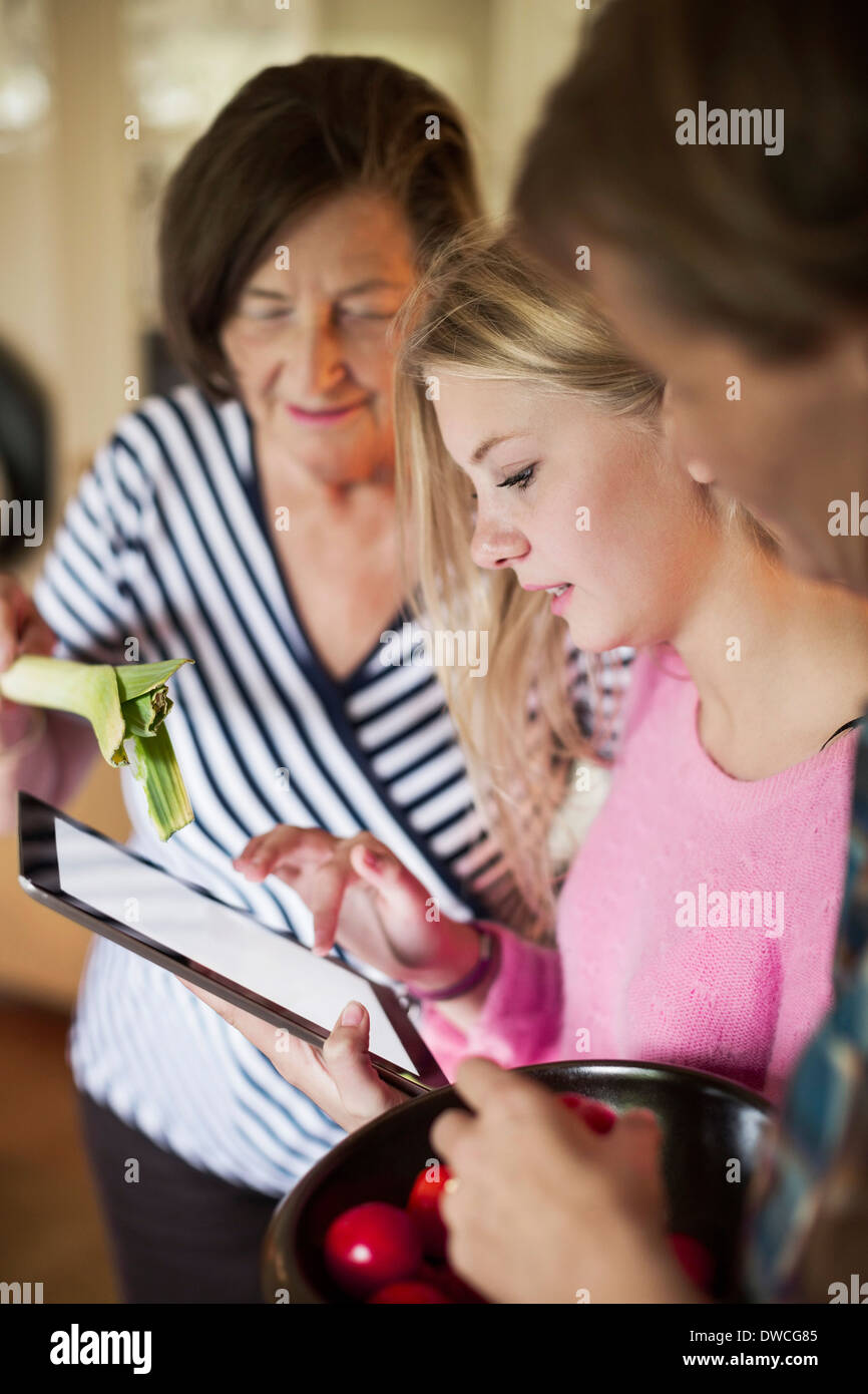 Three generation females checking out recipe on digital tablet in kitchen - Stock Image