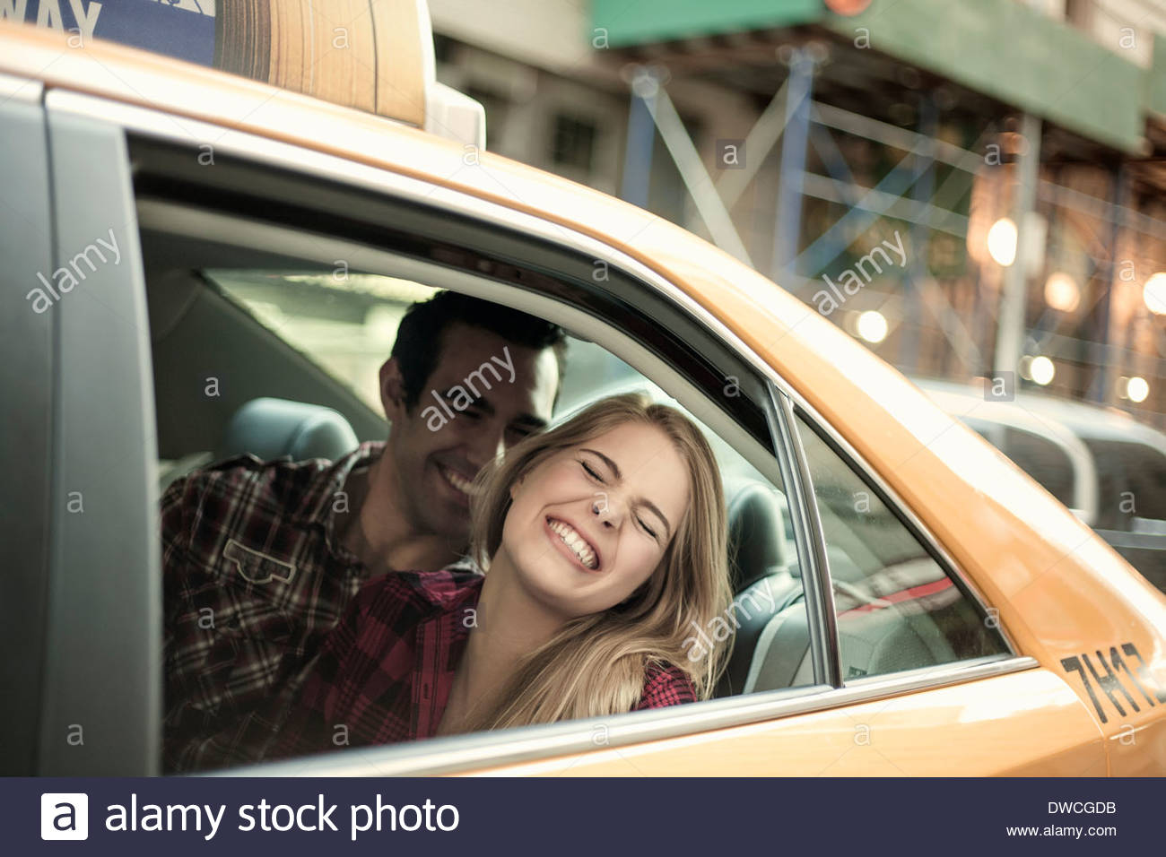 Young couple laughing in yellow cab, New York City, USA - Stock Image