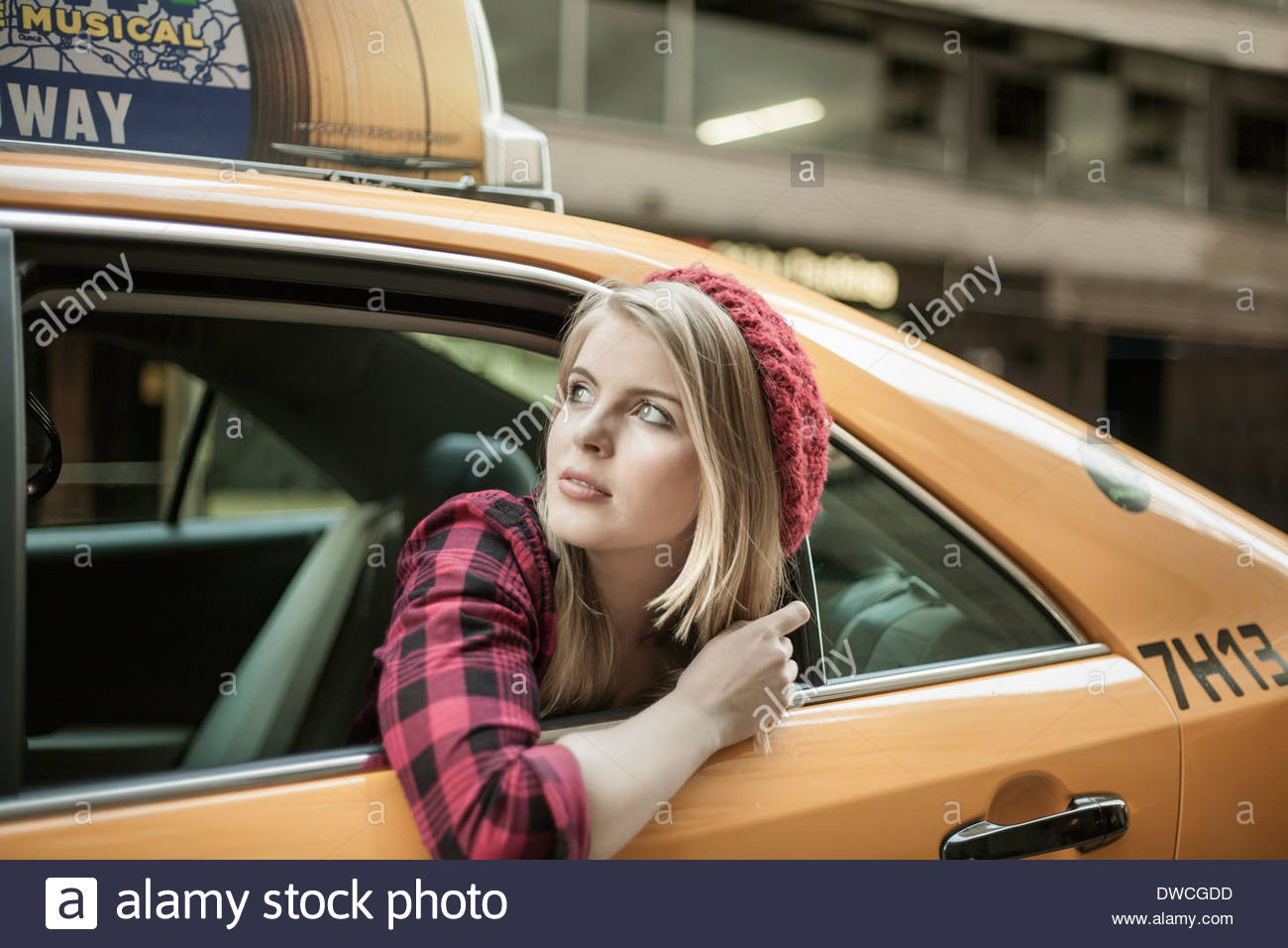 Young woman looking out from yellow cab, New York City, USA - Stock Image