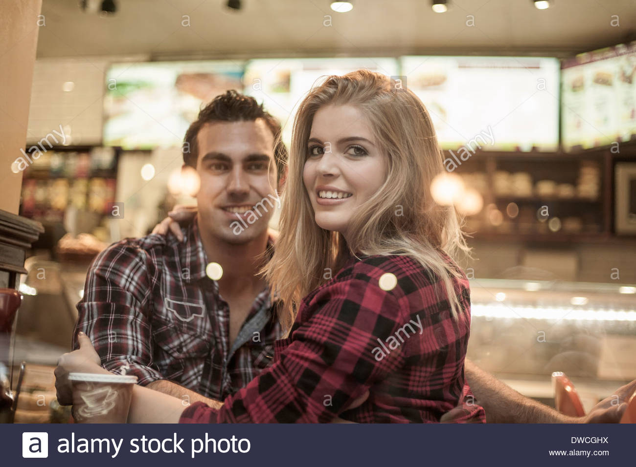 Young couple looking out of cafe window - Stock Image