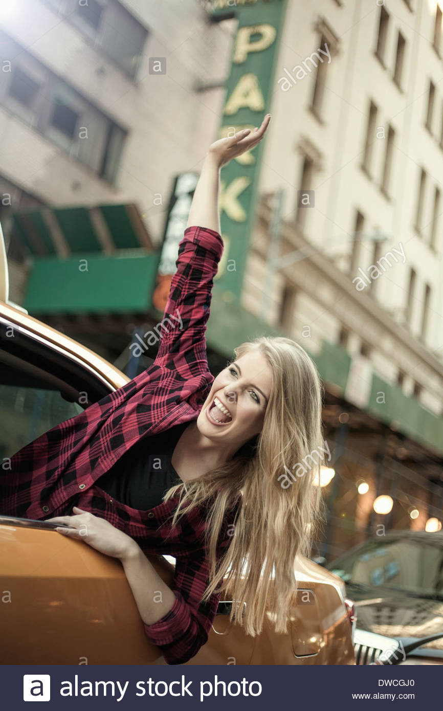 Young woman waving out from yellow cab, New York City, USA - Stock Image