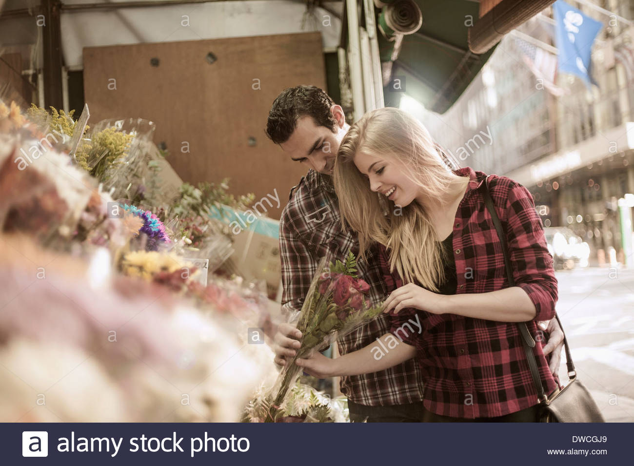 Young couple choosing flowers at flower stall - Stock Image