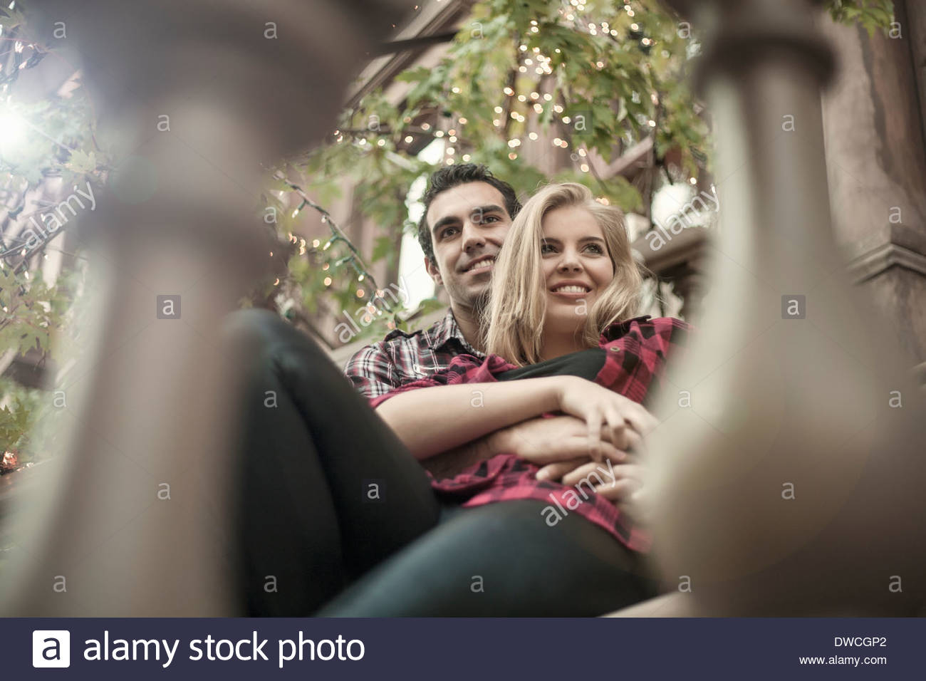 Romantic young couple sitting on traditional city apartment steps - Stock Image