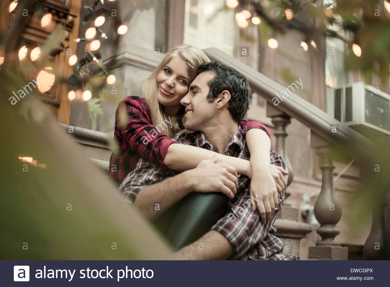 Happy couple sitting on traditional city apartment steps - Stock Image