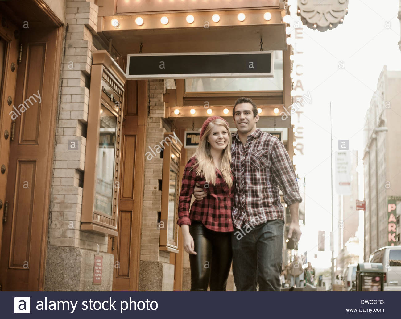 Young couple strolling outside theatre, New York City, USA - Stock Image