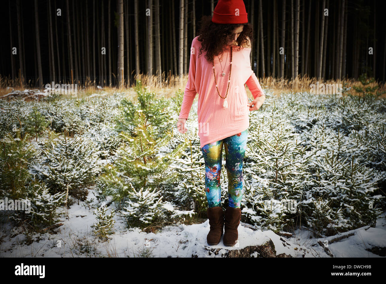 Mid adult woman in hat, standing on snow covered ground - Stock Image