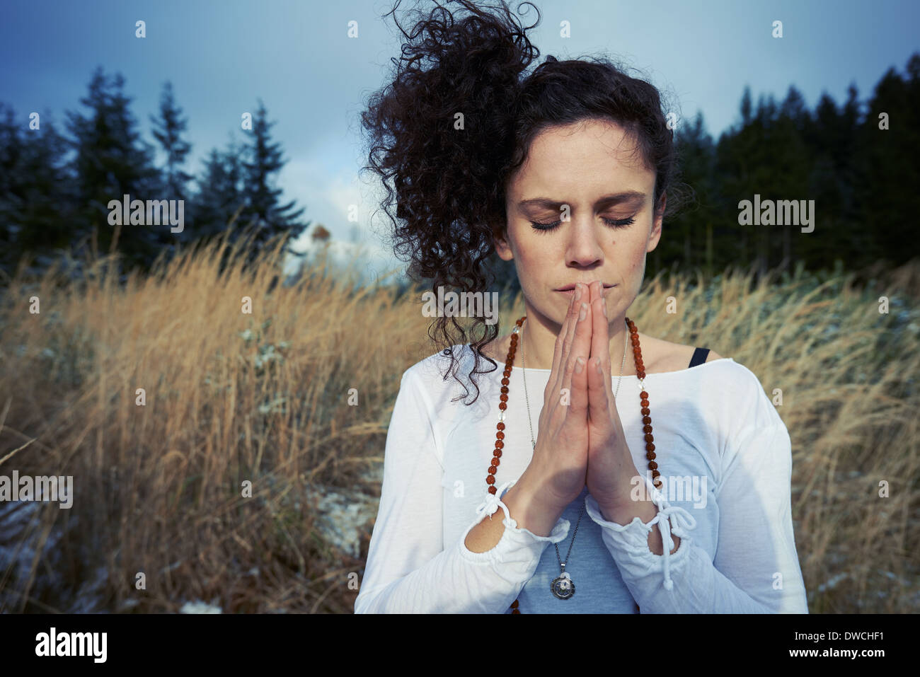 Mid adult woman meditating in forest - Stock Image