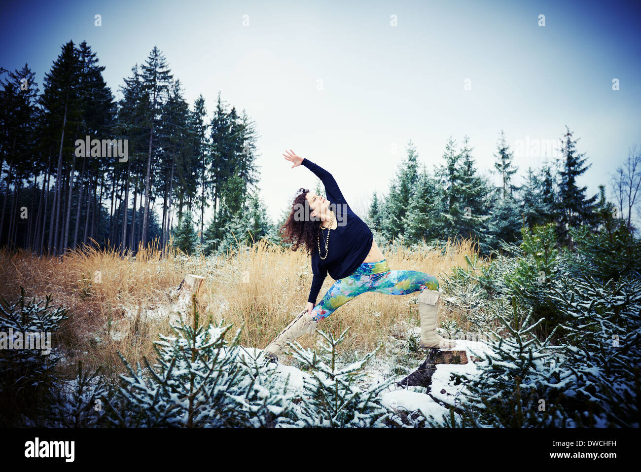 Mid adult woman practicing yoga in forest - Stock Image