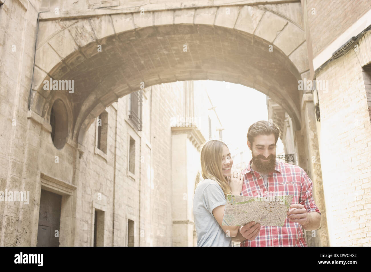 Young couple looking at map outside Valencia Cathedral, Valencia, Spain Stock Photo