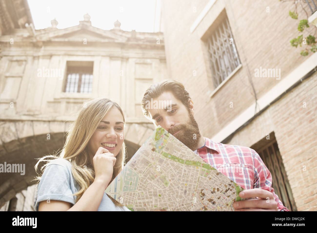 Young tourist couple looking at map outside Valencia Cathedral, Valencia, Spain Stock Photo