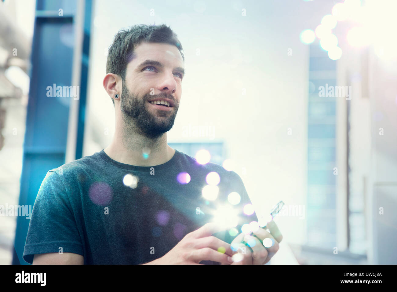 Mid adult man looking up at lights coming from smartphone - Stock Image