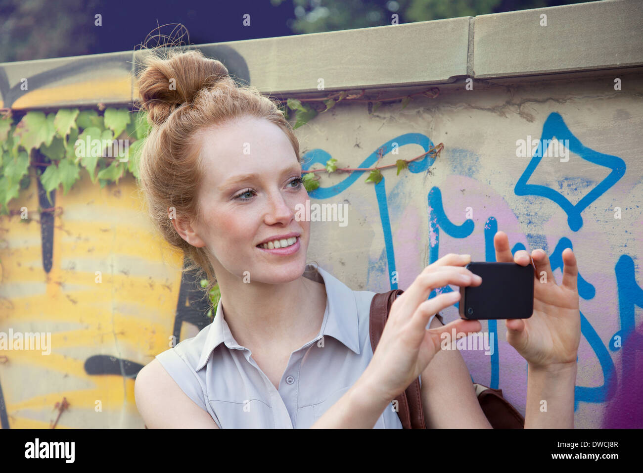 Young woman taking photograph on smartphone - Stock Image