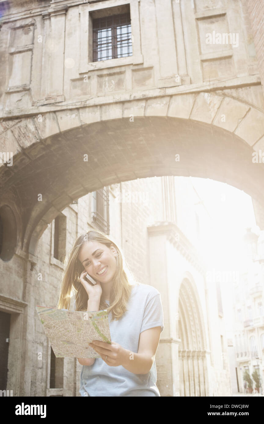Young woman looking at map outside Valencia Cathedral, Valencia, Spain Stock Photo
