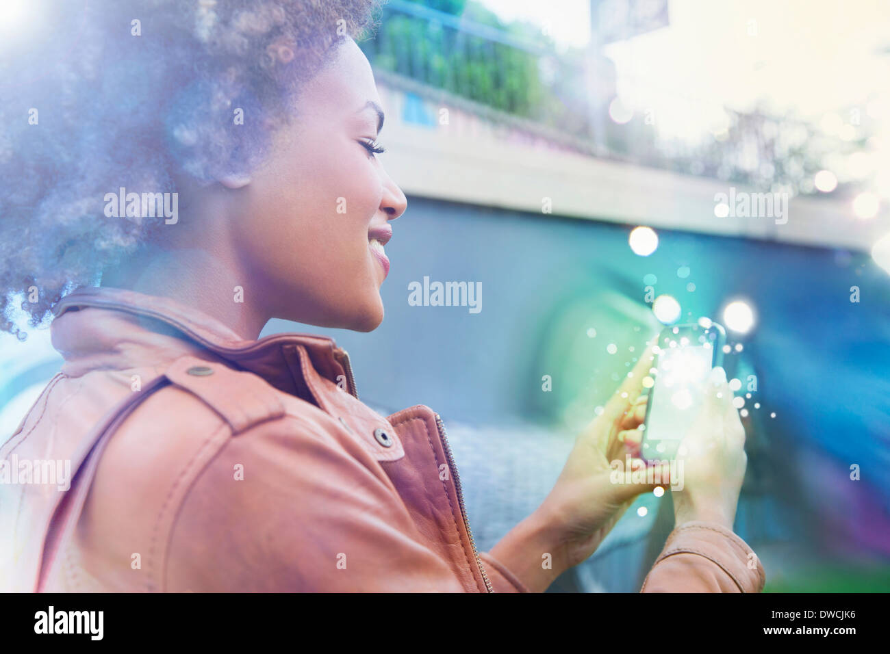 Young woman looking at smartphone with glowing lights coming out - Stock Image