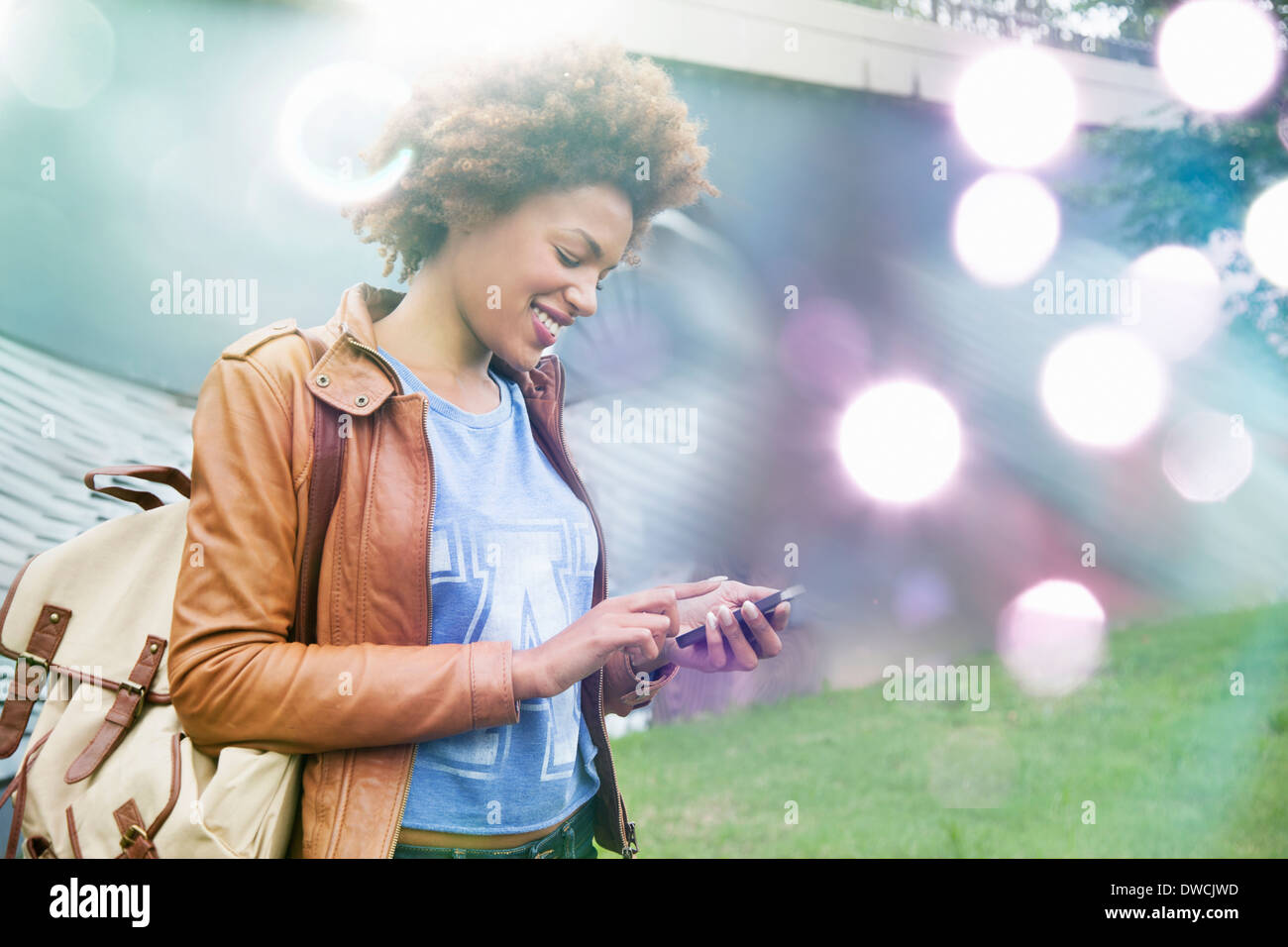 Glowing lights and young woman using smartphone - Stock Image