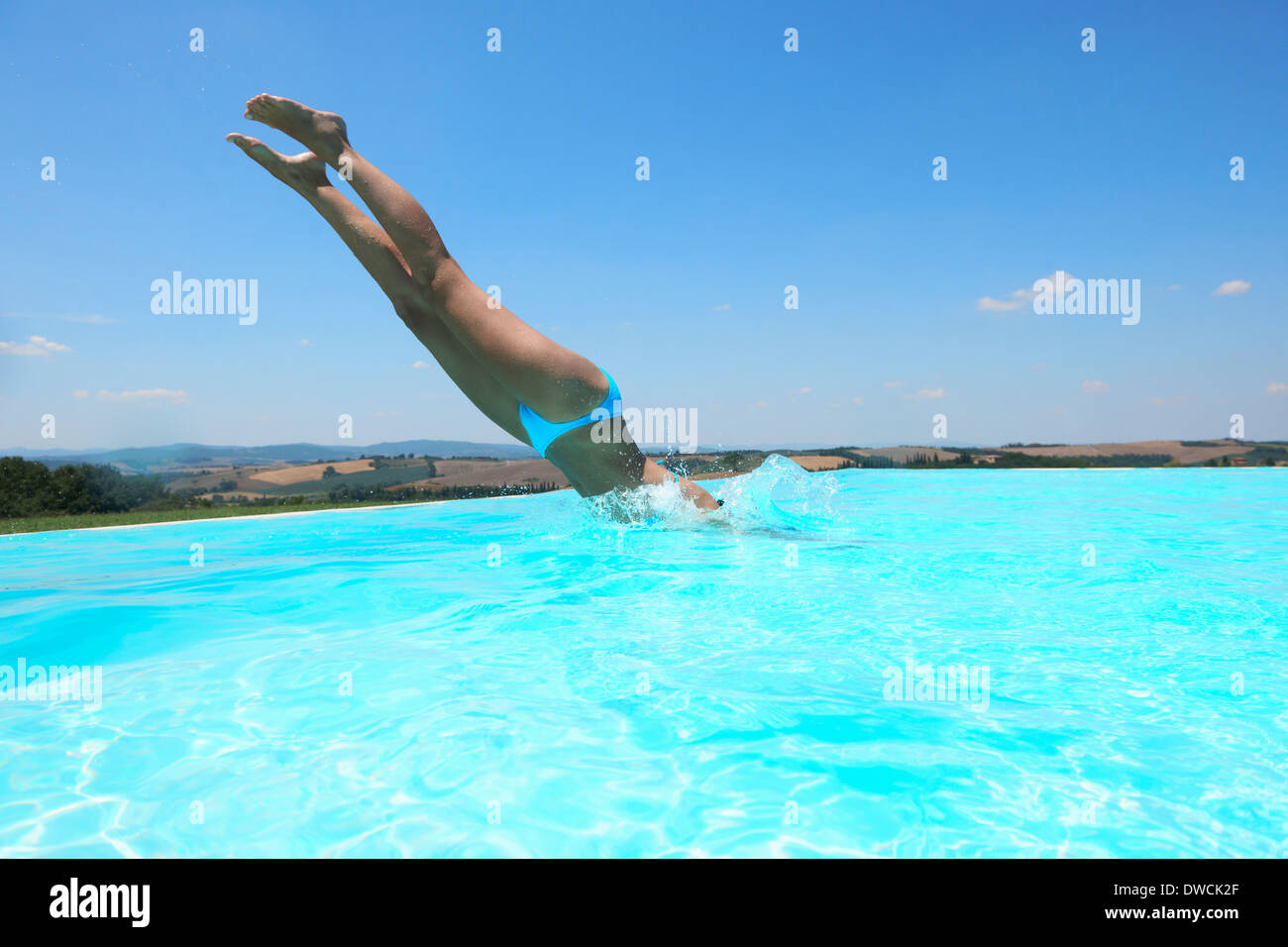 Mid adult woman diving into swimming pool - Stock Image