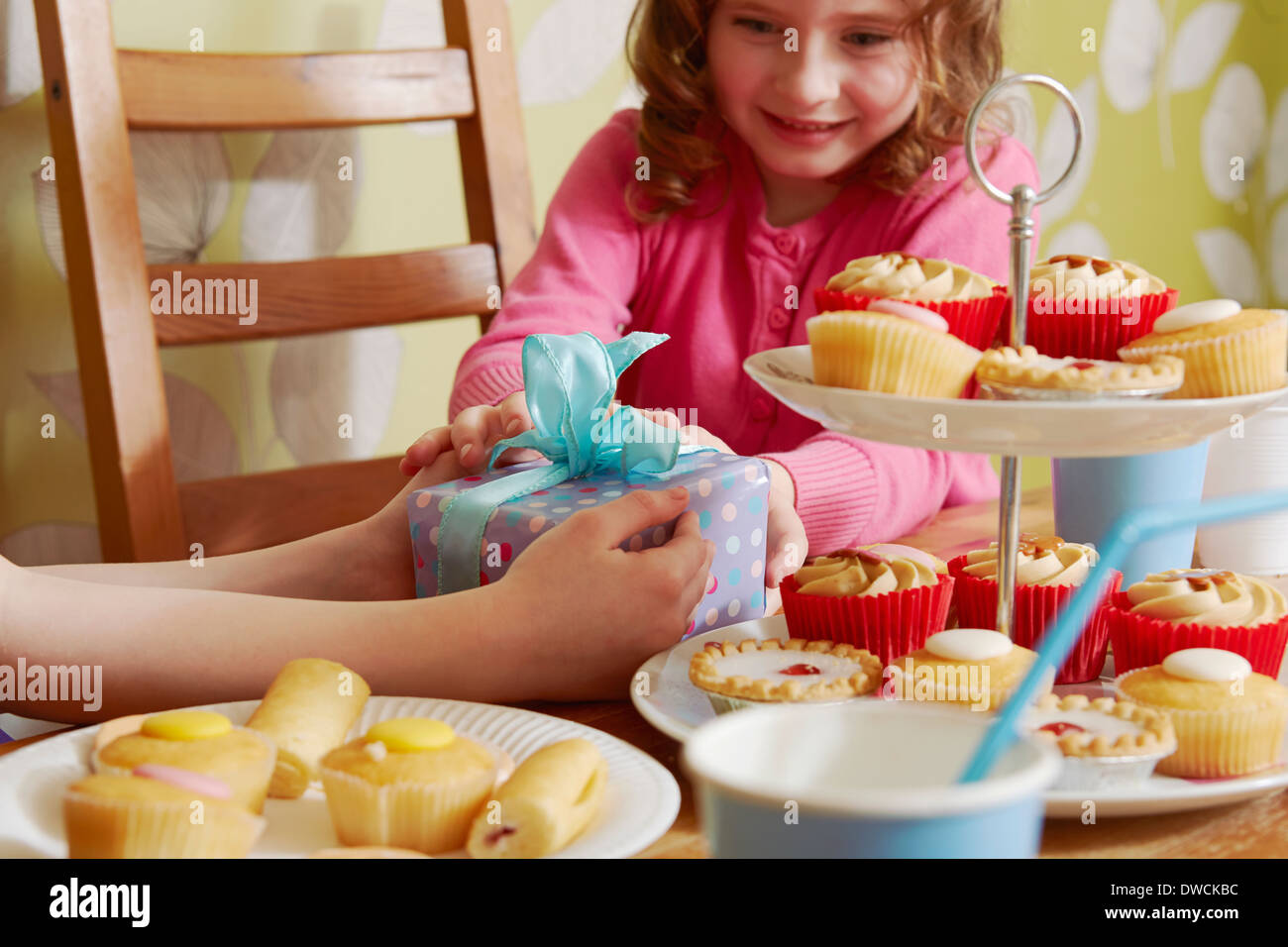 Girl receiving birthday present with cakes on cakestand - Stock Image