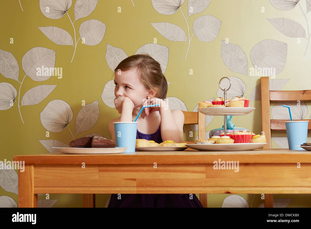 Bored looking girl at table with party food - Stock Image