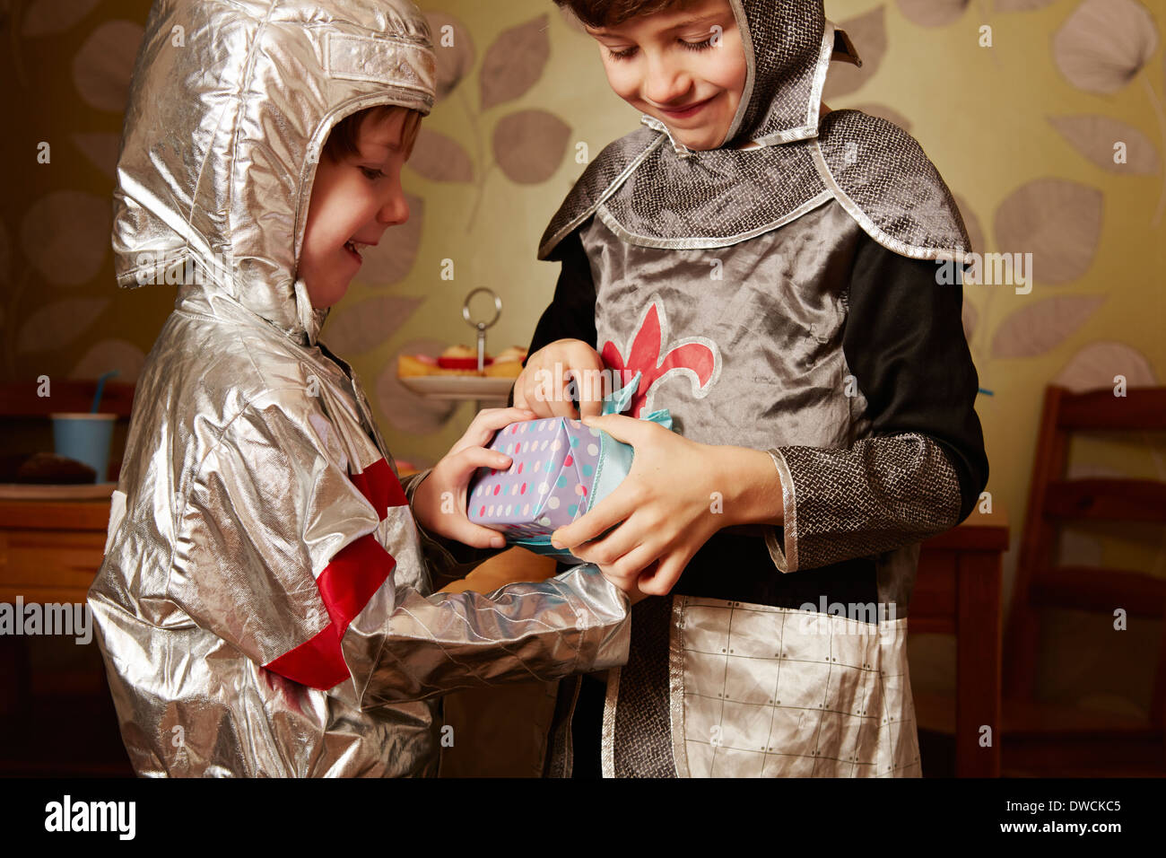 Two boys dressed as knights, one receiving birthday present - Stock Image