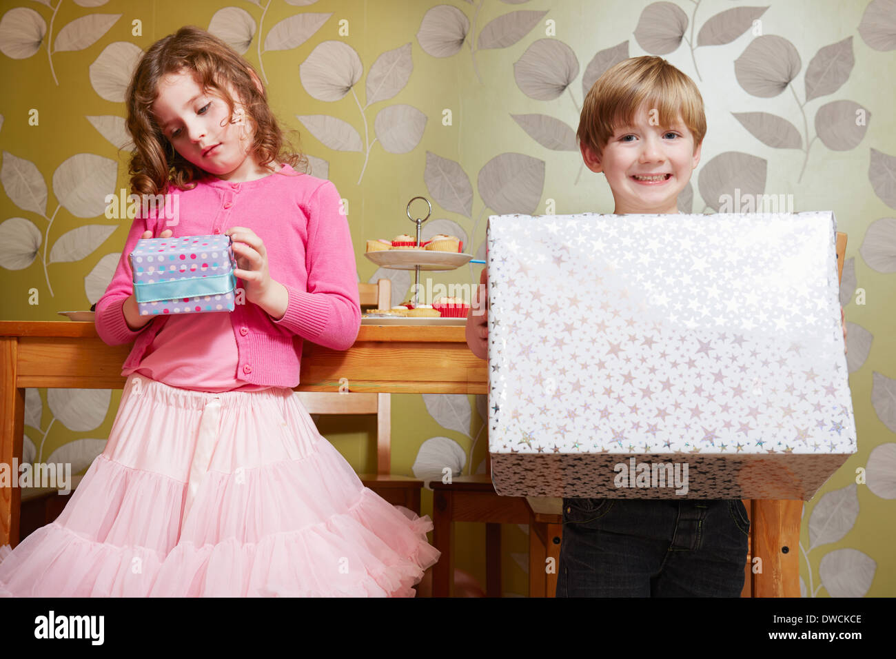 Boy and girl holding large and small present - Stock Image