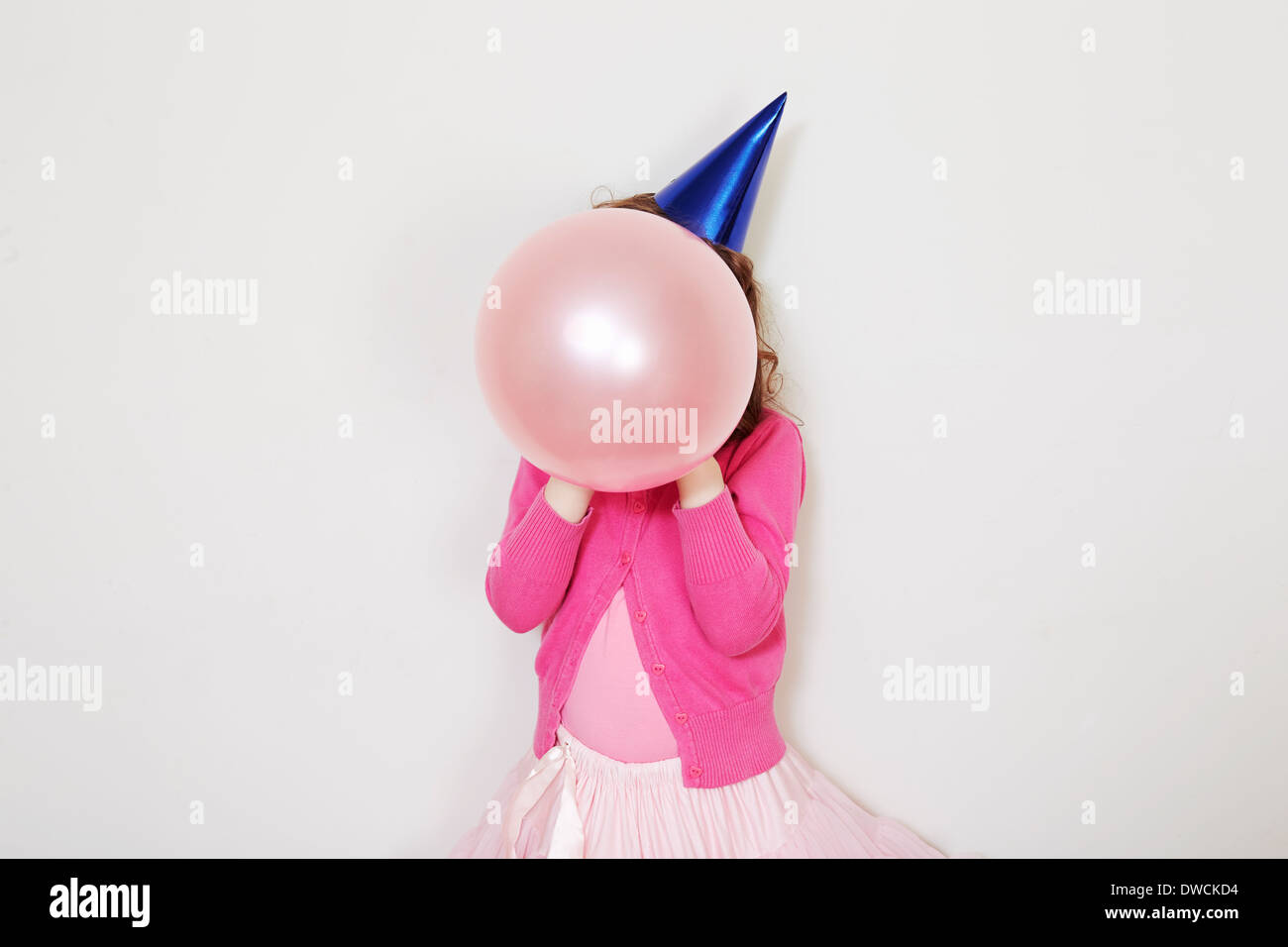 Girl holding pink balloon in front of face - Stock Image