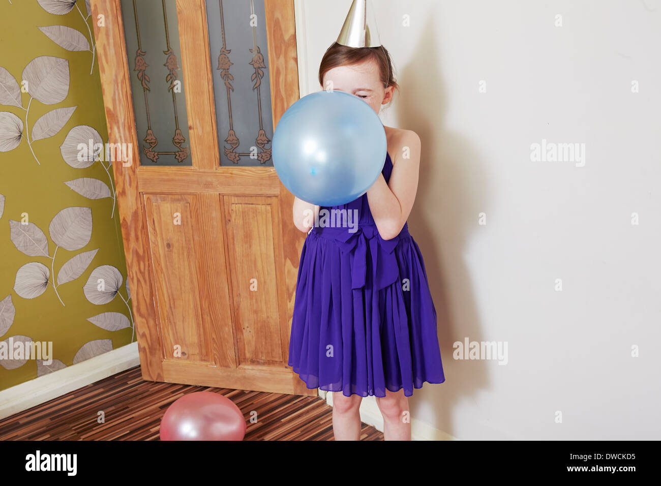 Girl blowing up blue balloon - Stock Image