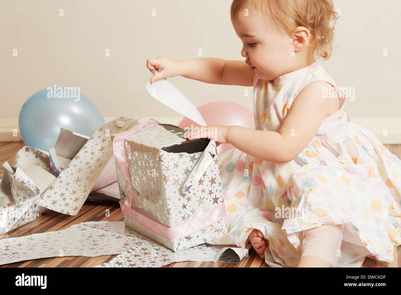 Toddler girl opening birthday present - Stock Image