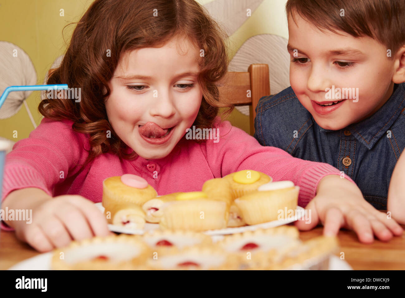 Girl staring at plate full of cakes, licking lips - Stock Image
