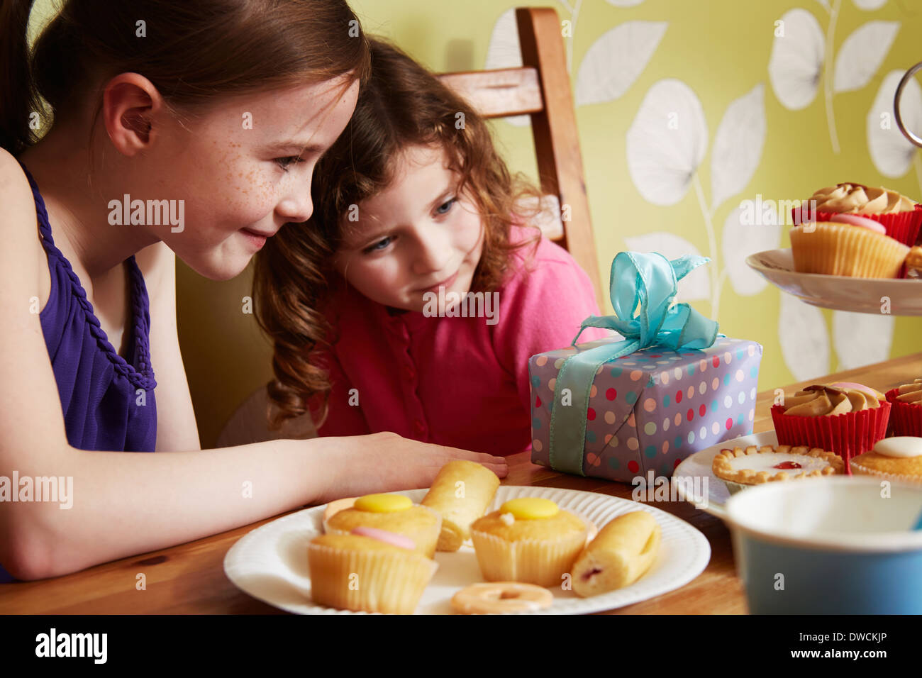Two girls looking at birthday present with plate of cakes - Stock Image