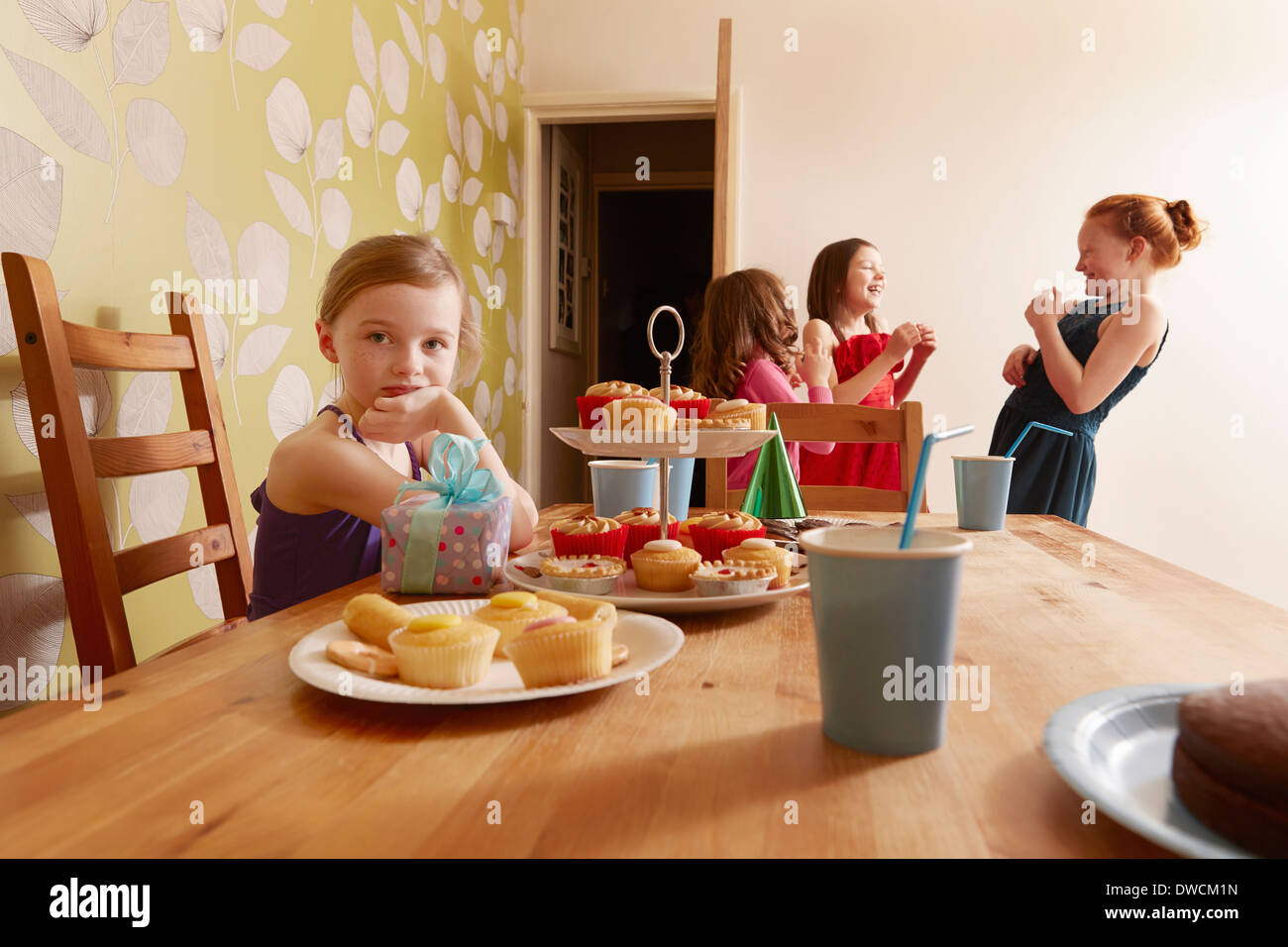Girl at table with party food, friends in background - Stock Image