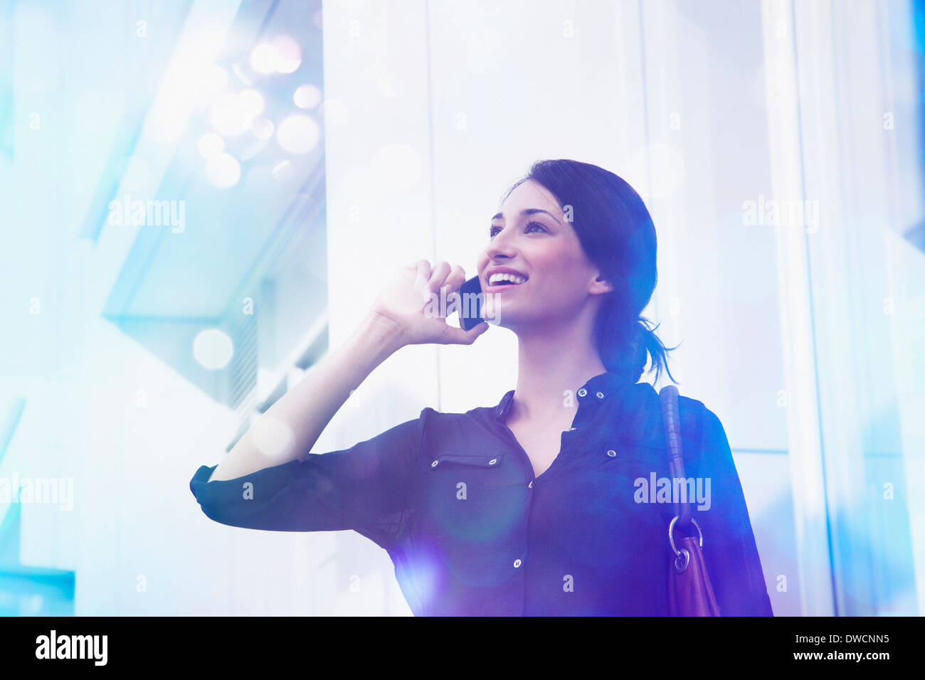 Young businesswoman talking on smartphone with lights coming out of it - Stock Image