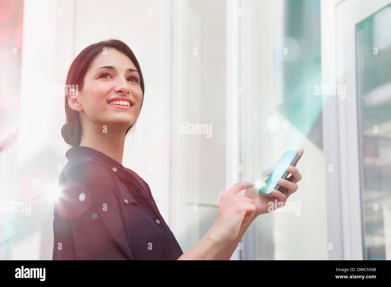 Young businesswoman holding smartphone with lights coming out of it - Stock Image
