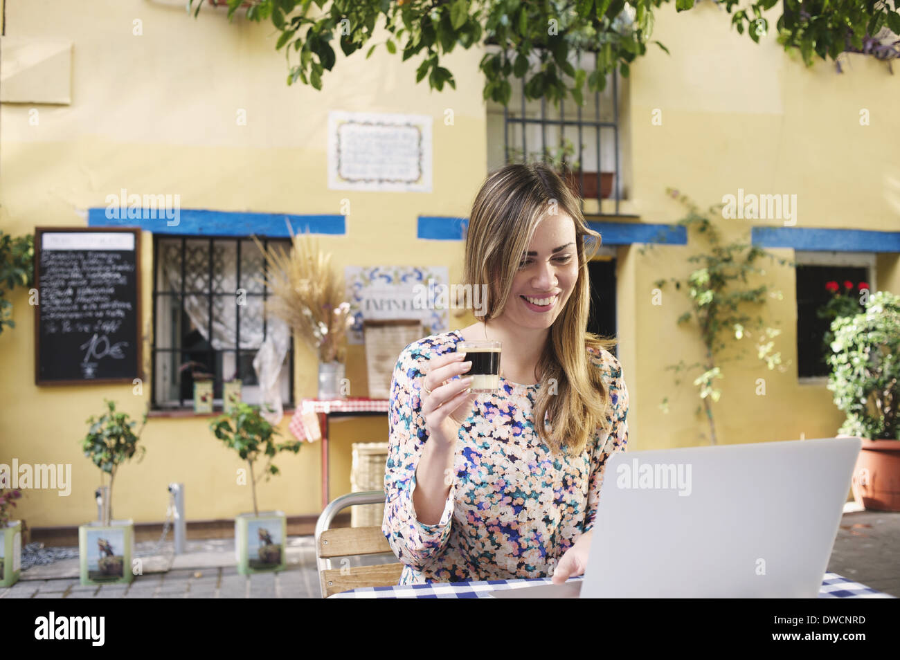 Young female tourist enjoying a break at sidewalk cafe, Valencia, Spain - Stock Image