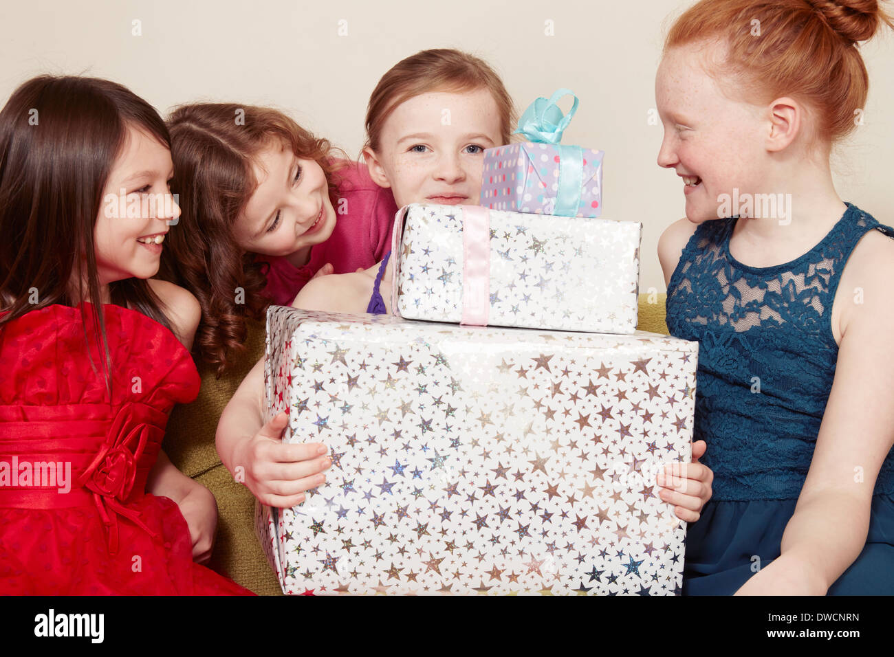 Girl holding birthday present with friends - Stock Image
