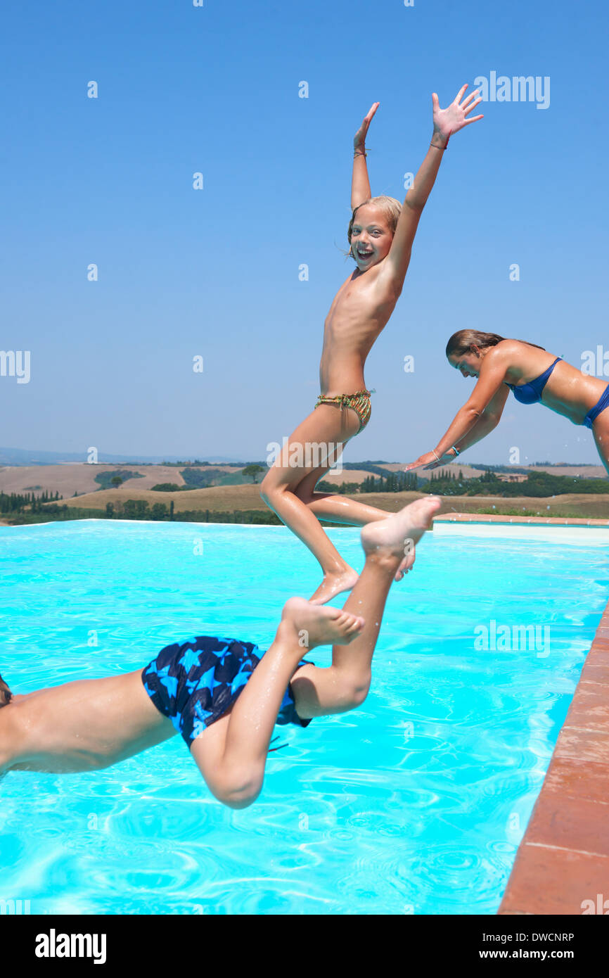 Three people jumping into swimming pool - Stock Image