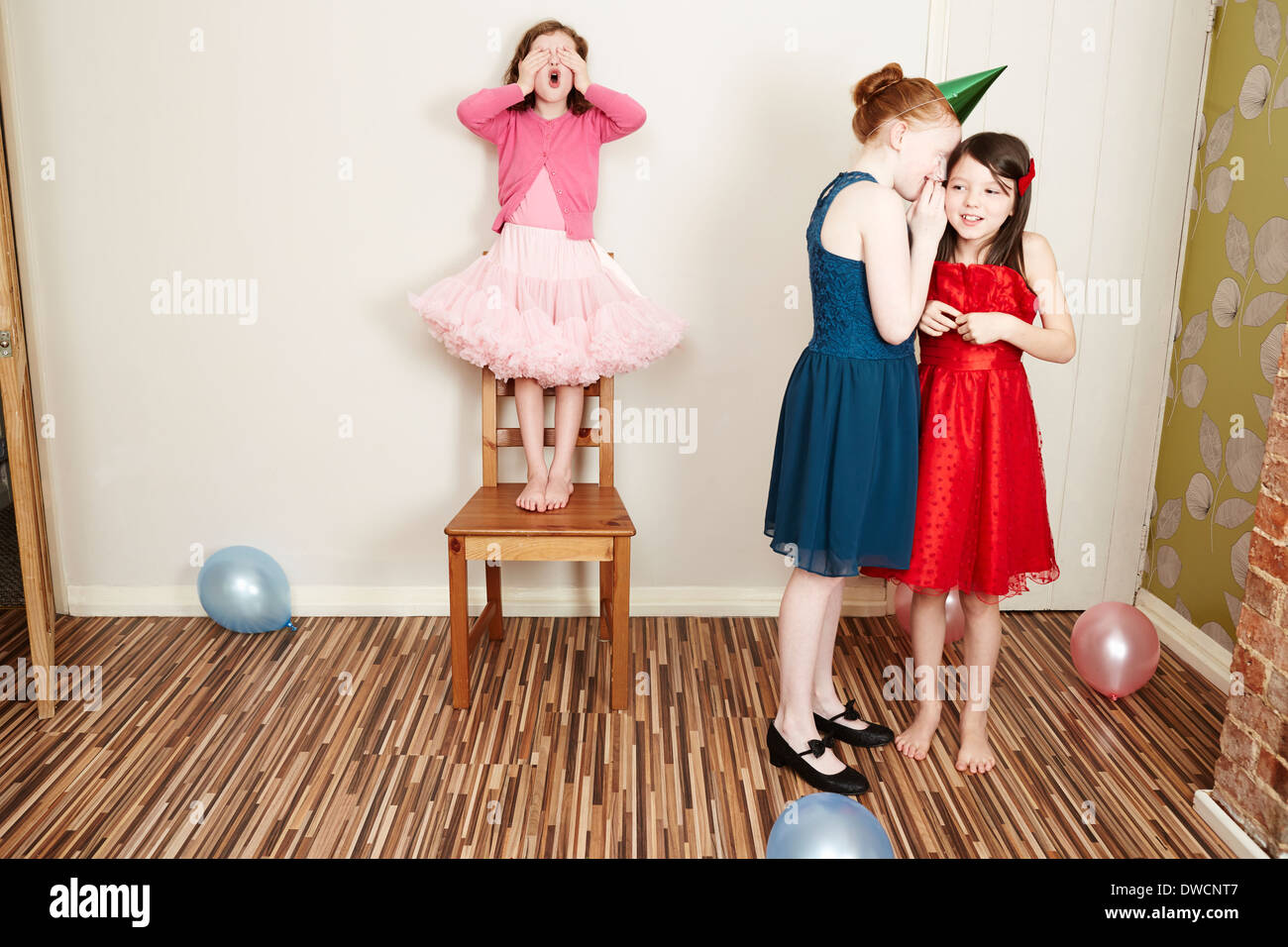 Three girls playing hide and seek at birthday party - Stock Image