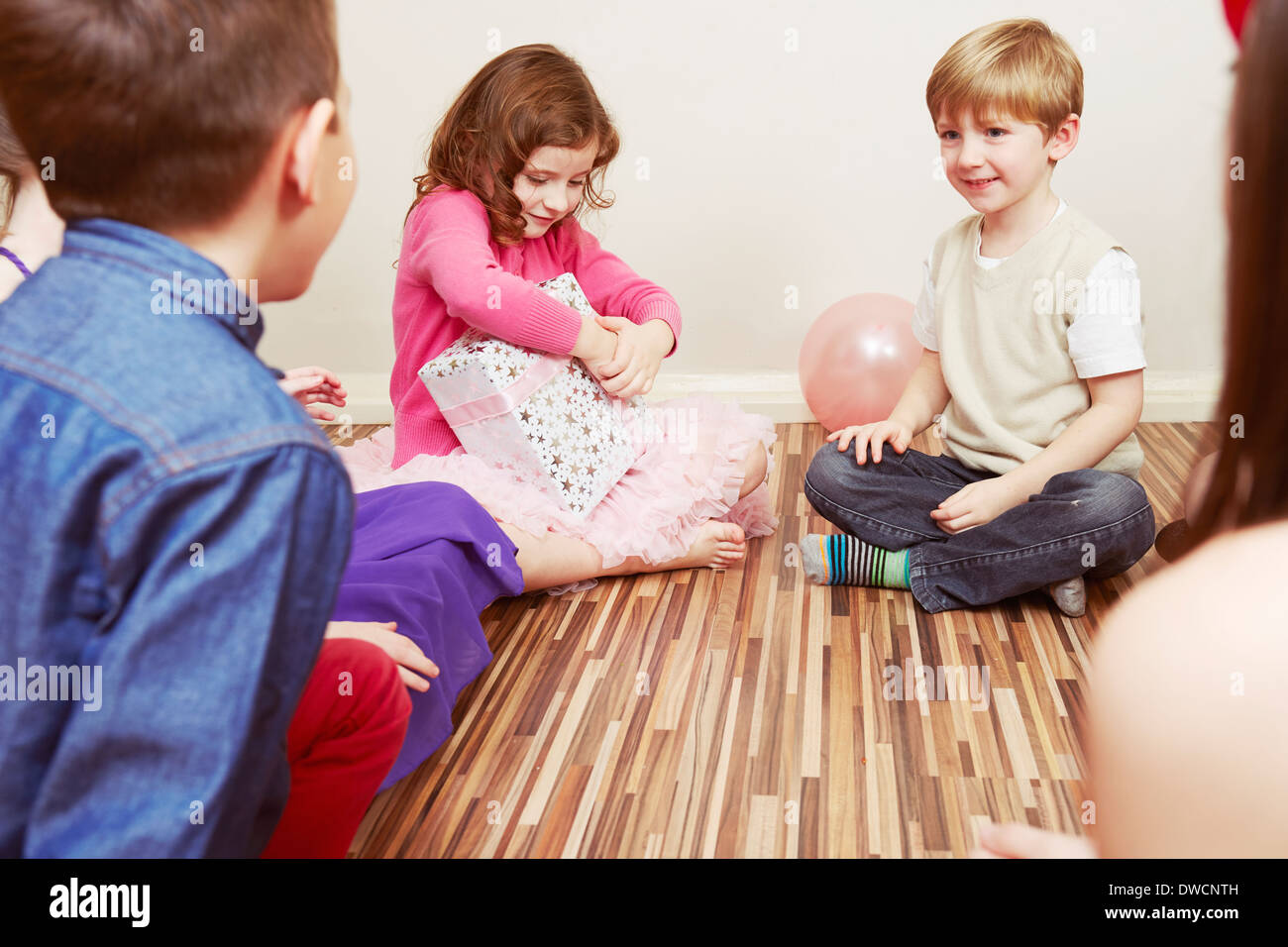 Children at party, girl holding birthday present - Stock Image