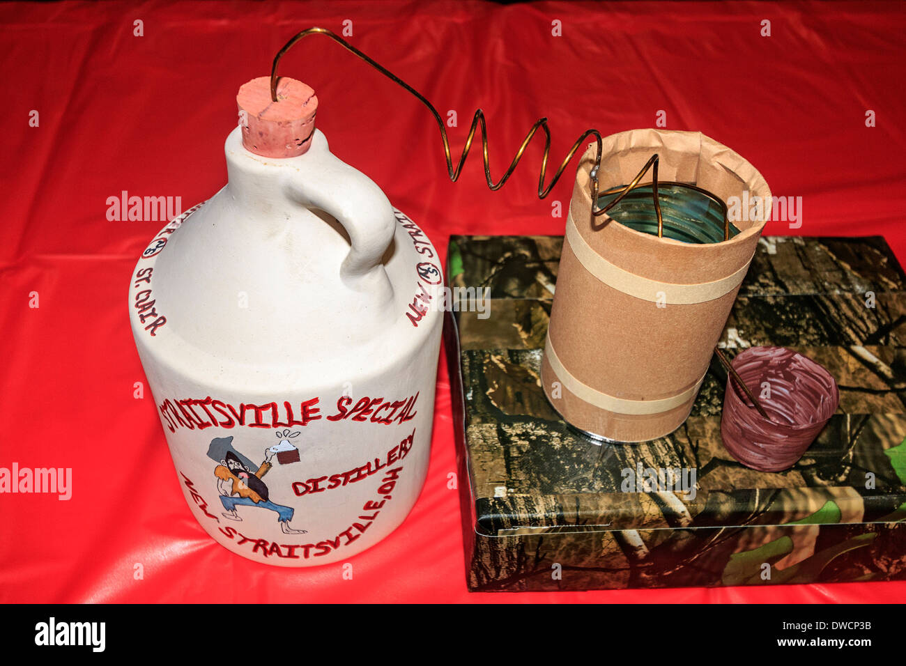 Decorative moonshine jug along with barrel and pail at Straitsville Special Distillery in New Straitsville, Ohio, USA. - Stock Image