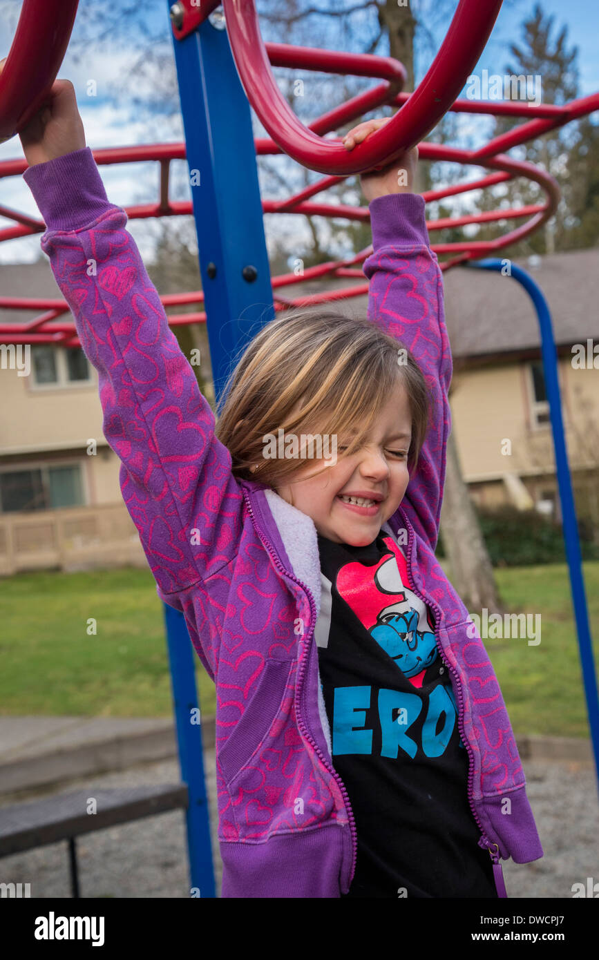 Child in playground on rings, bars. - Stock Image