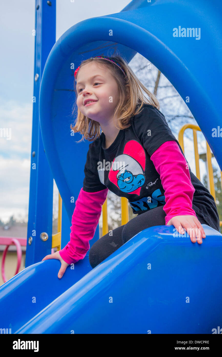 Child in playground at top of slide. - Stock Image