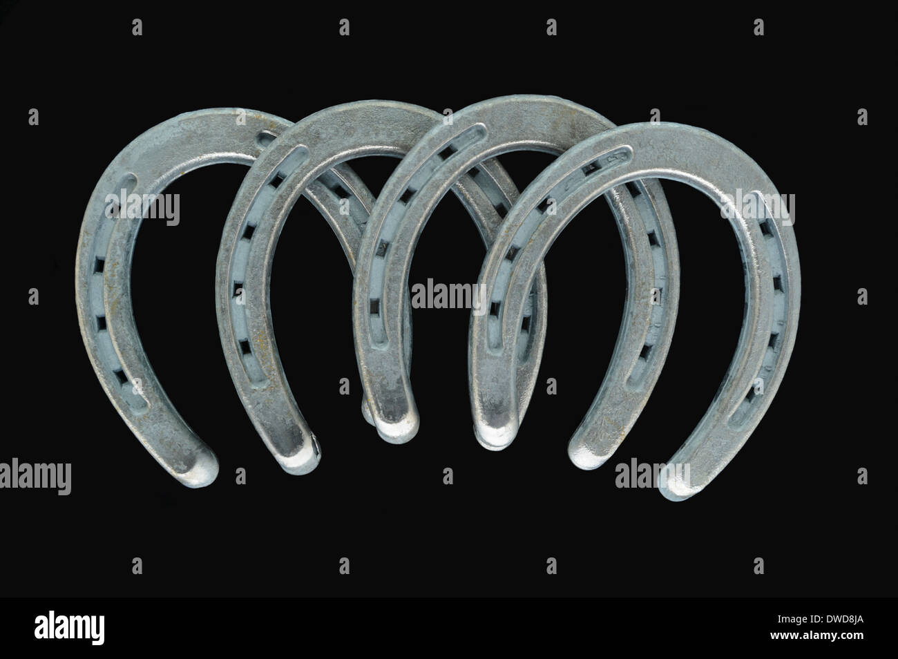 Four silver horseshoes, in a symmetrical arch for good fortune and luck, a simple studio shot on a black background. - Stock Image