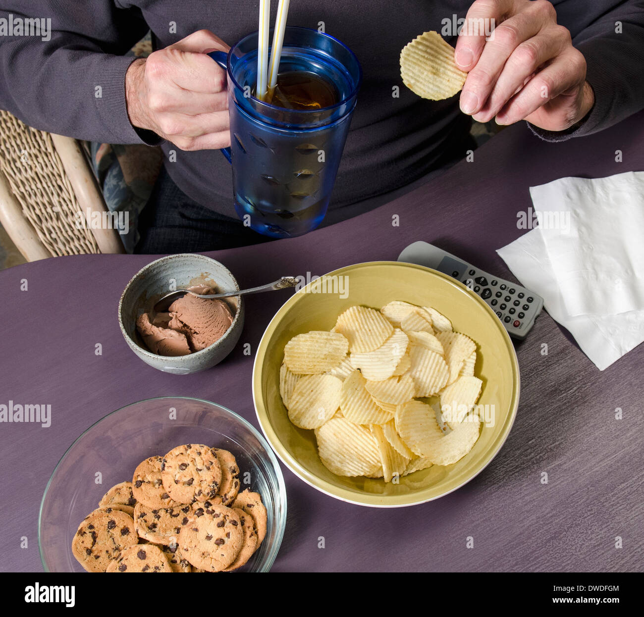 man eating junk food watching television - Stock Image
