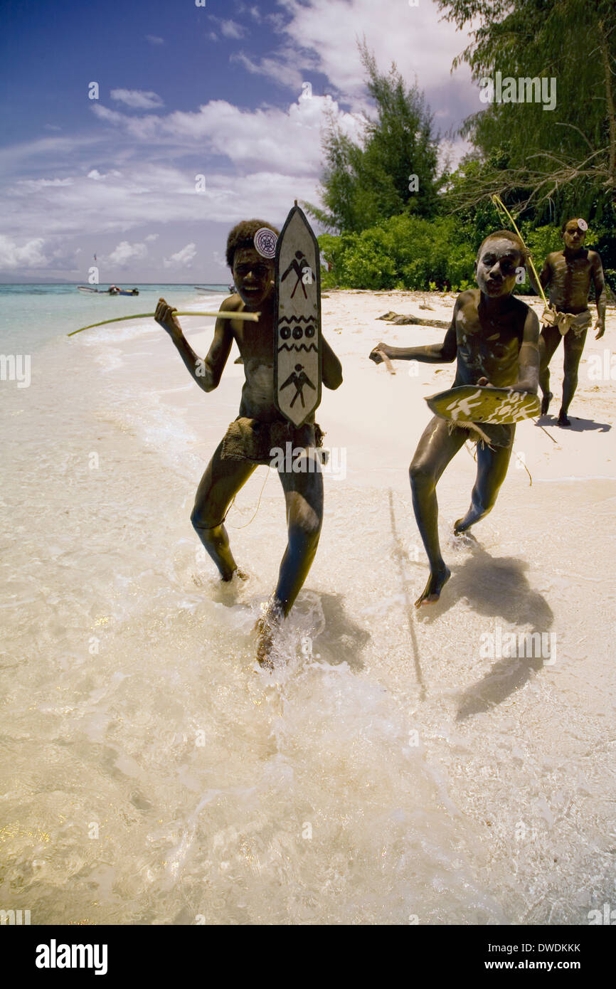 A group of young 'warriors' perform the customary welcome attack on Kennedy Island, Solomon Islands, South Pacific - Stock Image